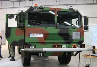 Вид макета неуправляемого реактивного снаряда калибра 122 мм и вид спереди демонстрационного варианта боевой машины WR-40 Langus