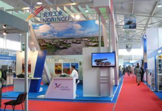 Стенд китайской корпорации Norinko. На экране кадр фильма с изображением боевой машины А100 для стрельбы реактивными снарядами к