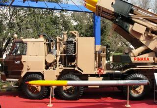 Частичный вид сбоку макета боевой машины Pinaka и макета неуправляемого реактивного снаряда калибра 214 мм