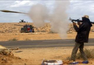 Повстанец-боевик в Ливии стреляет из противотанкового гранатометв во время столкновений с силами про-Каддафи
