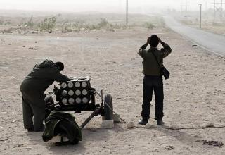 Один повстанец наводит установку, а другой наблюдает за районом через бинокль в Brega, 4 марта 2011 г. REUTERS/Goran Tomasevic