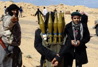 Боевик повстанцев несет выстрелы для РПГ около Bin Jawad, 6 марта 2011 года