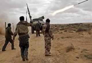 Боевики повстанцев жестикулируют во время стрельбы БМ-21 в бою на дороге между Ras Lanuf и Bin Jawad. Goran Tomasevic/Reuters