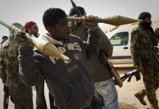 Ливийский повстанец несет выстрелы на КП на фронтовой линии около Zwitina, пригород Ajdabiya, юг Benghazi. 24.03.2011 г. фото АР