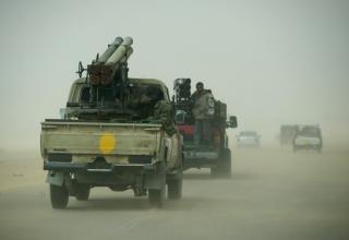 Боевики повстанцев и гражданские лица движутся через песчаную бурю, т.к. они спасаются бегством из Аджабии. 7 апреля 2011 года