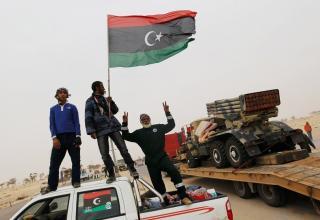 Ливийские повстанцы наблюдают за отводом военной техники на шоссе. 7 апреля 2011 г. Ливия. Аджабия.