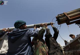 Повстанцы заряжают установку на дороге в районе фронтовой линии в Бреге. 05.04.2011 г. REUTERS/Youssef Boudlal