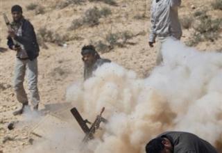 Ливийские повстанцы стреляют ракетой из установки по силам про-Каддафи вдоль линии фронта около Бреги, 5.04.2011 г.