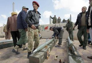 Боевики повстанцев подготавливают НУРС для заряжания боевой машины. Пол пути между Брегой и Аджабией. 9.04.11 г. (AP/Ben Curtis)