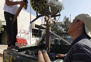 Боевики повстанцев заряжают блок орудий в составе артчасти на шасси автомобиля на КПП в Бир Аййад. (Bir Ayyad). Reuters.