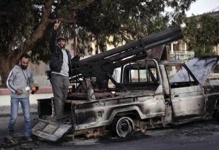 Боевики повстанцев обследуют сгоревшую боевую машину. http://www.dailymail.co.uk/