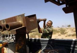 Боевик, воюющий против сил Гаддафи заряжает самодельную установку во время боя около г.Сирт.26.09.11. REUTERS/Goran Tomasevic