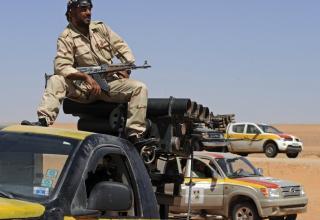 Боевик Ливийского НПС смотрит за порядком во время патрулирования около Wadi Bei, около Мисрата. Francisco Leong / AFP/