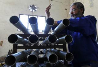Ливийский повстанец-механик старается зафиксировать элемент оружия, захваченного у сил Кадхафи, в Мисрата,10.08.11.