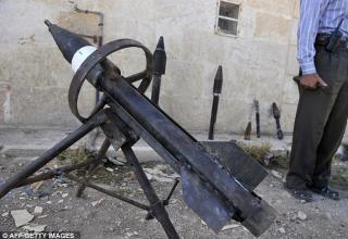 Изготовитель оружия Abu al-Fadhel показывает различное самодельное оружие среди которого ракетная установка. www.dailymail.co.uk