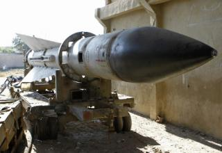 Мужчина идет около ракеты 25.12.2012г. Армейские барака за  Дамаском. Ракета захвачена Свободной Армией Сирии.