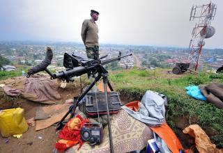 Боевик повстанцев М23, смотрящий на г.Бунагана с захваченного военного поста на высоте. Peter Greste/Al Jazeera