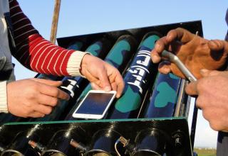 Повстанцы используют компас смартфона, чтобы прицелить самодельную зенитку, у военаэропорта Менах, окраина Алеппо. 17.02.2013 г.