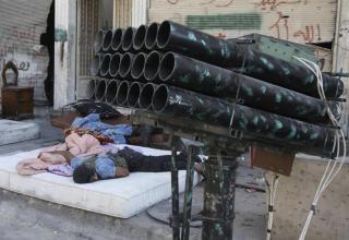Боевик ССА отдыхает около ракетной установки в районе Bustan al-Basha Алеппо 25.07.2013 г. REUTERS/Muzaffar Salman. trust.org