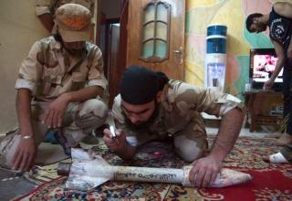 Член ССА пишет имя бойца-соратника на самодельной ракете в Deir al-Zor.16.06.2013 г.http://www.militaryphotos.net.Khalil Ashawi