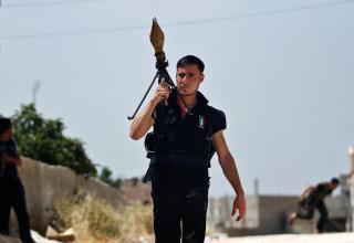 Боевик ССА несёт РПГ во время боестолкновений с сирийскими войсками около Идлиба, Сирия 15.06.2012 г. (AP Photo/Khalil Hamra).