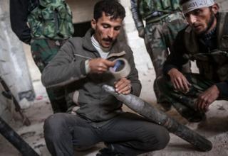 Боевик сирийских повстанцев готовит к пуску самодельную ракету по зданию ВВС около Алеппо. 17.11.2012 г. Narciso Contreras/AP.