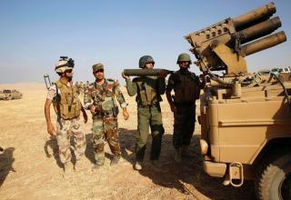 Боевик курдского Peshmerga заряжает БМ РСЗО во время боя с исламистами в Zummar, около Мосула 15.09.14. REUTERS/Ahmed Jadallah.